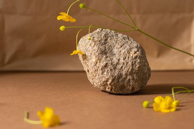 Composição de vida minimalista bege marrom com material natural pedra flor selvagem cor amarela abstra ...