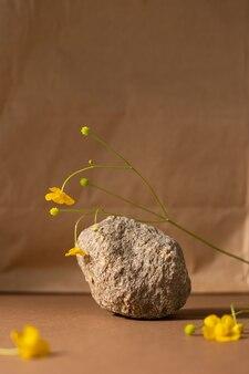 Composição de vida minimalista bege marrom com material natural: pedra, flor selvagem cor amarela, conceito de design de arte moderna abstrata copyspace plataforma fundo vertica