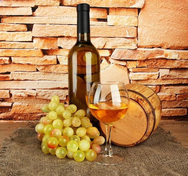 Composição de vinho, barril de madeira e uvas na mesa no fundo da parede de tijolos