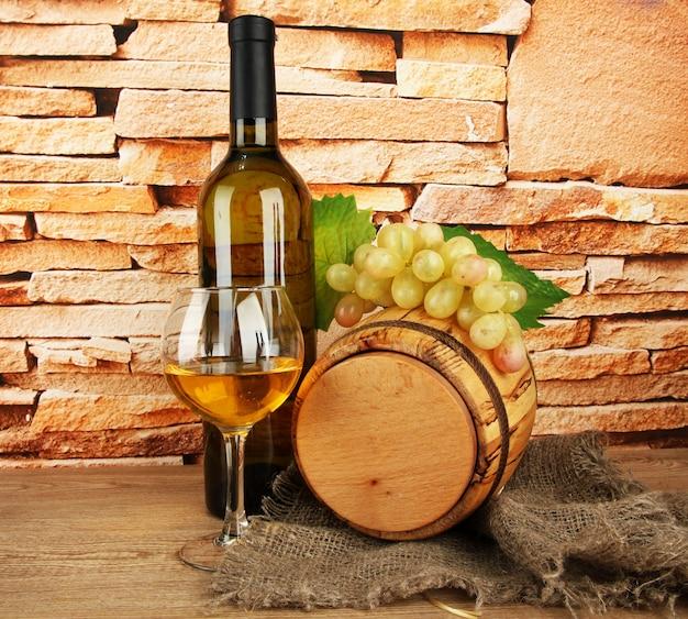 Composição de vinho e uvas em barril de madeira na mesa na parede de tijolos