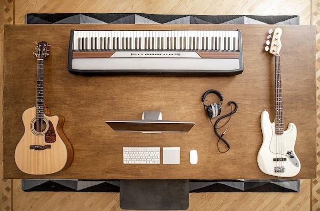 Composição de violão, baixo, teclas musicais, computador e fones de ouvido em uma grande mesa de madeira.