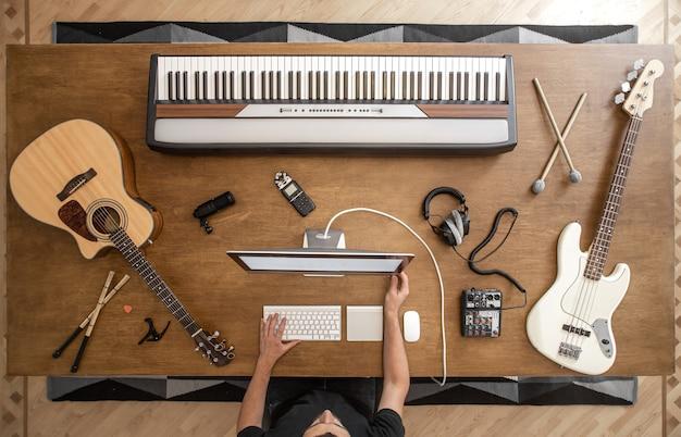 Composição de vista superior de um músico no computador e instrumentos musicais e detalhes sobre uma mesa de madeira.