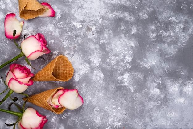 Composição de waffles de sorvete com buquês de rosas em um fundo de pedra