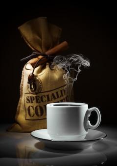 Composição de xícara branca e saco de grãos de café
