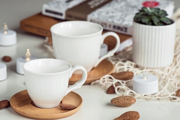 Composição de xícaras de chá de café branco e nozes de amêndoa