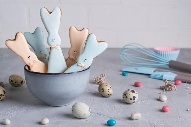 Composição decorativa de primavera páscoa com biscoitos caseiros de páscoa em forma de um coelho engraçado, ovos de codorna e ferramentas necessárias para fazer bolos de gengibre. .