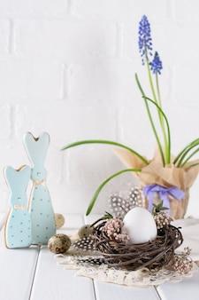 Composição decorativa de primavera páscoa com ovo de galinha branca em um ninho com flores. decorações de férias. configuração de mesa festiva de páscoa