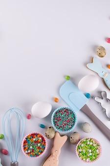 Composição decorativa de primavera páscoa. fazendo biscoitos de açúcar caseiros. biscoito em forma de um coelho engraçado, ferramentas necessárias para fazer bolos de gengibre, granulado colorido.