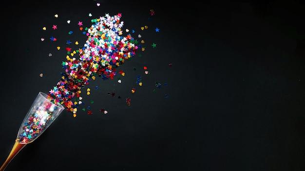 Composição do ano novo com confetes coloridos em vidro