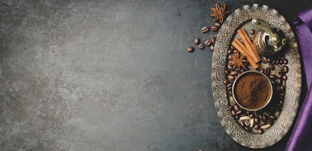 Composição do café com o moedor de café manual vintage em fundo preto de concreto