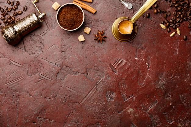 Composição do café com o moedor de café manual vintage sobre fundo vermelho de concreto