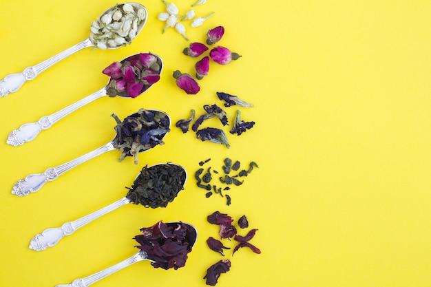 Composição do chá. diferentes variedades de chá nas colheres de prata no amarelo
