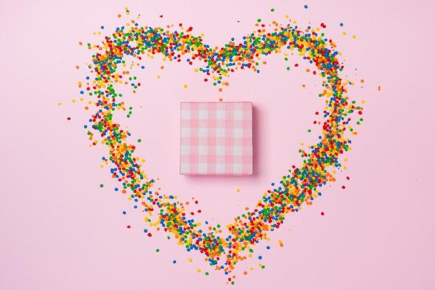 Composição do dia dos namorados: caixa de presente com coração arco, doces e balas na cor de fundo.