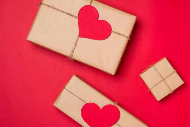 Composição do dia dos namorados: caixa de presente com laço e corações em fundo vermelho.