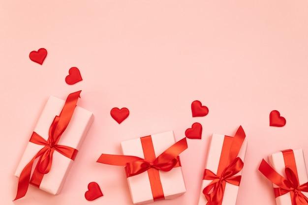 Composição do dia dos namorados com presentes surpresa com laço vermelho e forma do coração em um fundo rosa com copyspace