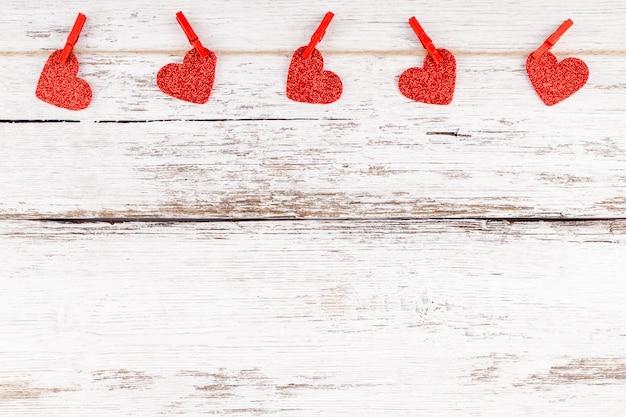 Composição do dia dos namorados: corações vermelhos em fundo dourado glitter