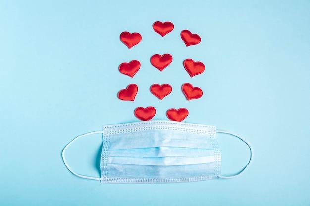 Composição do dia dos namorados. máscara protetora de rosto médica e muitos corações vermelhos sobre fundo azul. novo normal e coronavírus, conceito covid-19. postura plana.