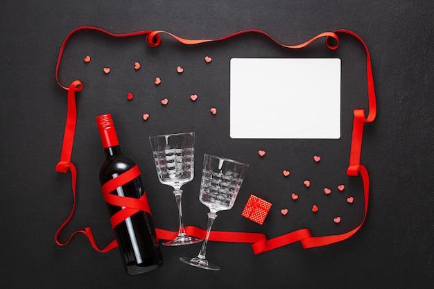 Composição do dia dos namorados. vinho e duas taças, um presente e uma folha em branco para um desejo, um presente e corações vermelhos