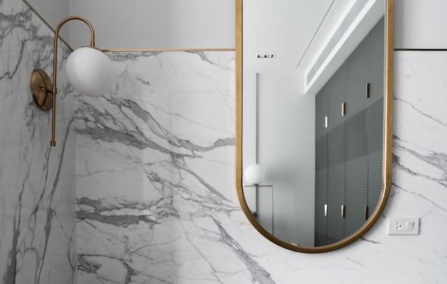 Composição do espelho de ouro inoxidável com parede de mármore branco e luminária de parede de ouro