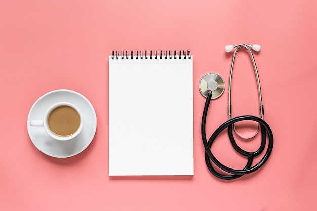 Composição do estilo do minimalismo com xícara de café, bloco de notas em branco e estetoscópio médico na opinião superior do fundo rosa.