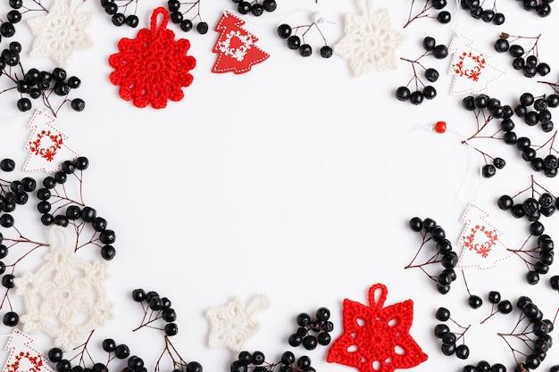 Composição do feriado de natal. padrão de vermelho preto festivo criativo, ramos de bagas de chokeberry, férias de decoração vermelha de natal, confetes dourados sobre fundo branco. camada plana, vista superior