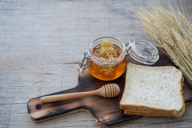Composição do frasco e do dipper do mel na tabela rústica. fundo de alimentos. saúde, comida, pão