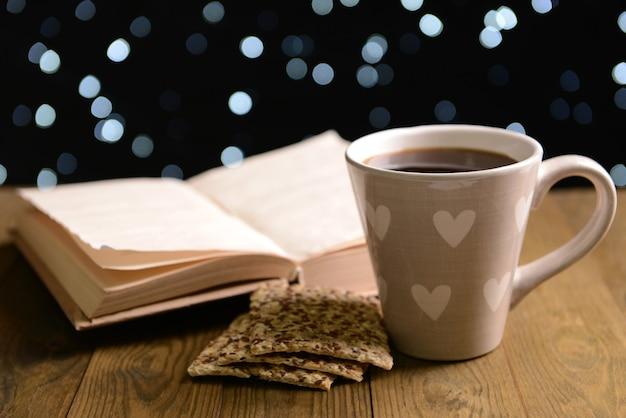 Composição do livro com uma xícara de café na mesa em fundo escuro
