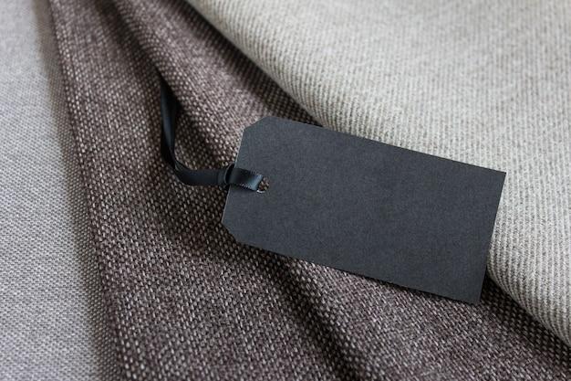 Composição do modelo de maquete de camadas de tecido marrom e etiqueta de preço de papel preto em branco