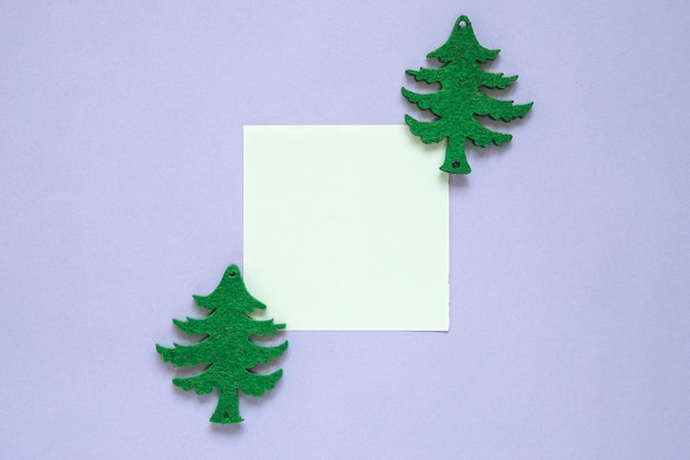 Composição do natal com nota pegajosa e árvores de natal