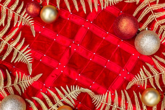 Composição do natal - decorações do ouro, folhas brilhantes e samambaia do ramo na vista superior.