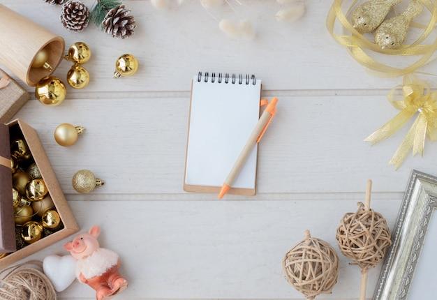 Composição do natal e tela vazia no papel do bloco de notas no fundo branco de madeira.