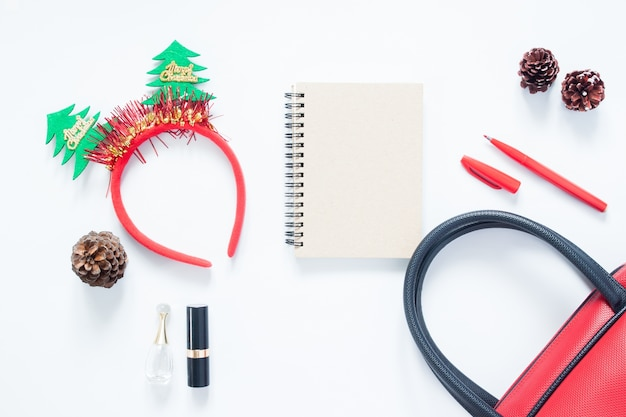 Composição do natal. moda de natal para meninas, cosméticos, saco, cones de pinho, notebook e caneta vermelha com espaço para cópia. flat lay, top view