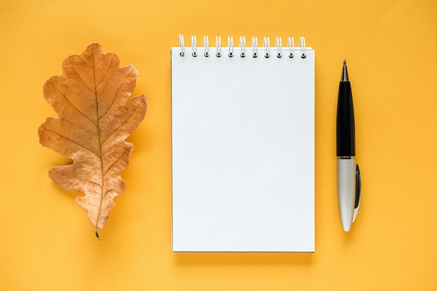 Composição do outono. bloco de notas em branco branco, folha de carvalho laranja seca e caneta em amarelo