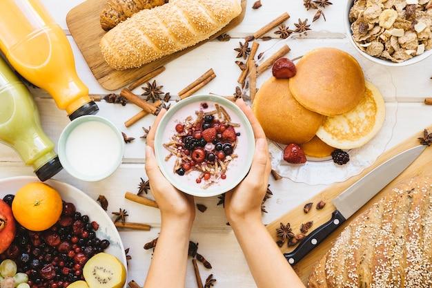 Composição do pequeno almoço com as mãos segurando tigela de iogurte