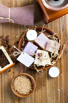 Composição do sabão caseiro do café, sal do mar em uma bacia e feijões de café em uma tabela de madeira marrom.