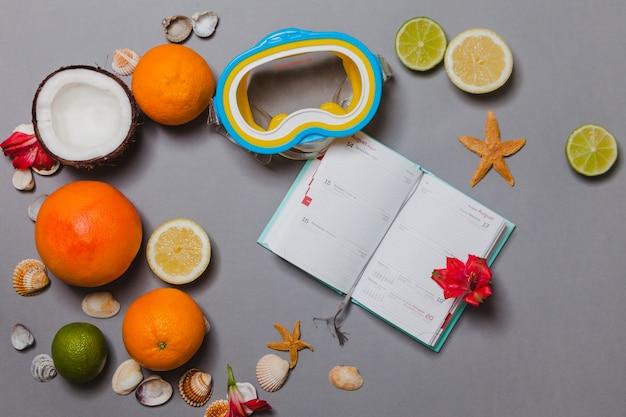Composição do verão com frutas cítricas, coco, óculos e diário