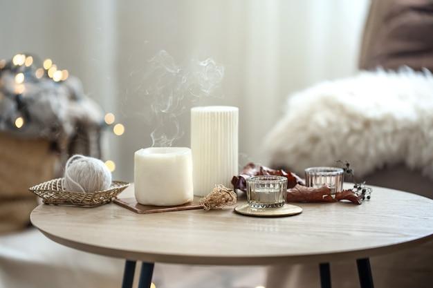 Composição doméstica em estilo escandinavo com velas no fundo desfocado com bokeh.