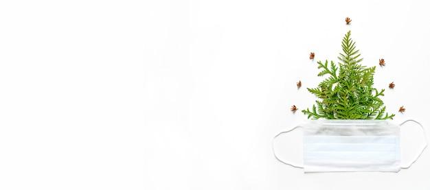 Composição dos galhos de thuja sob a forma de uma árvore de natal e uma máscara médica isolada em uma parede branca. o conceito de ano novo durante o vírus corona covid-19. espaço para texto. bandeira