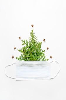 Composição dos galhos do thuja sob a forma de uma árvore de natal e uma máscara médica isolada em um fundo branco. conceito do ano novo durante o vírus corona covid-19.