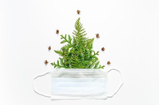 Composição dos galhos do thuja sob a forma de uma árvore de natal e uma máscara médica isolada em um fundo branco.