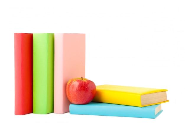 Composição dos livros escolares e uma maçã isolada na madeira branca