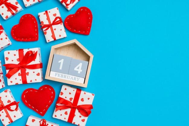 Composição dos namorados de caixas de presente, calendário de madeira e corações vermelhos de têxteis