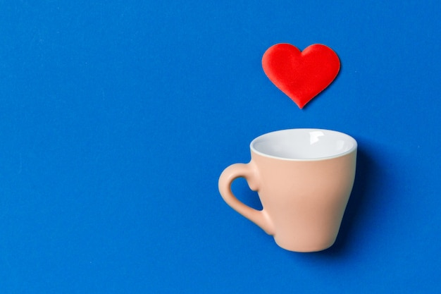 Composição dos namorados de coração vermelho, caindo de um copo