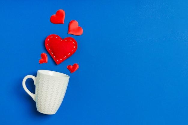 Composição dos namorados de corações vermelhos, caindo de um copo