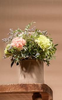 Composição ecológica em estilo hygge com buquê de flores em vaso de papelão diy em pé na velha mesa de madeira sobre fundo bege com espaço de cópia.