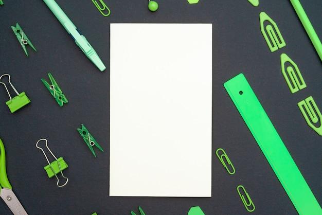 Composição educacional, artigos de papelaria. livro branco em branco. artigos de papelaria verde em um fundo preto. vista plana leiga, superior, copyspace.