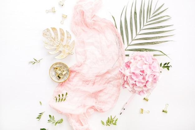 Composição elegante com buquê de flores de hortênsia rosa, folha de palmeira tropical, manta pastel, placa de folha de monstera e acessórios na superfície branca
