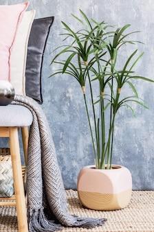 Composição elegante de aconchegantes detalhes do interior da sala de estar e travesseiros elegantes e coloridos. parede cinzenta criativa e piso em parquet. estilo escandinavo.
