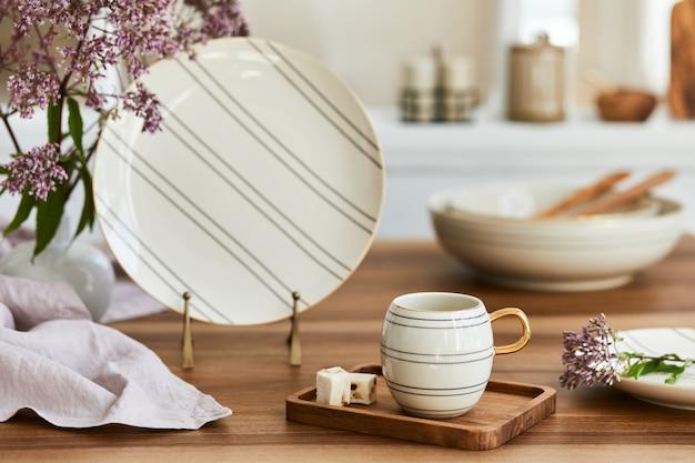 Composição elegante de design de interiores de sala de jantar elegante com mesa rústica, porcelana bonita, flores e acessórios de cozinha. beleza nos detalhes. modelo.