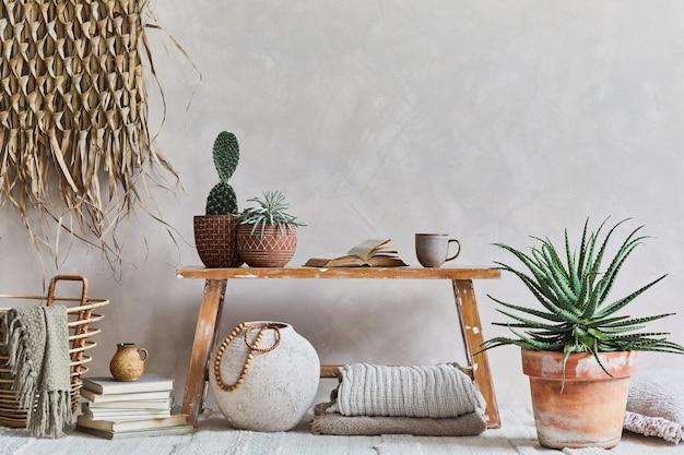 Composição elegante de interior aconchegante de sala de estar com espaço de cópia, banco em estilo retro, vaso de barro, louças, decoração de parede de palha e têxteis. inspiração rústica. vibes do verão. parede bege. modelo.